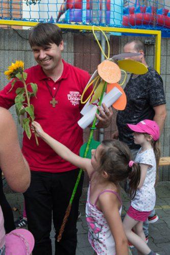 Kind reicht Pater Johannes eine Blume